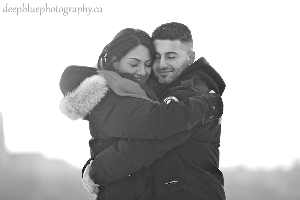 Engagement Photo of Couple Hugging in Winter Jackets