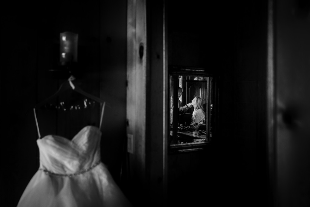 Photo of the bride getting her makeup done with her wedding dress hanging up
