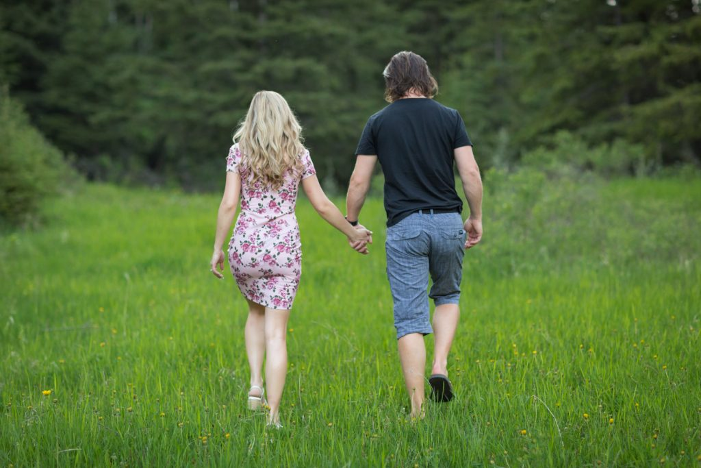 Engagement photo of couple walking through a field