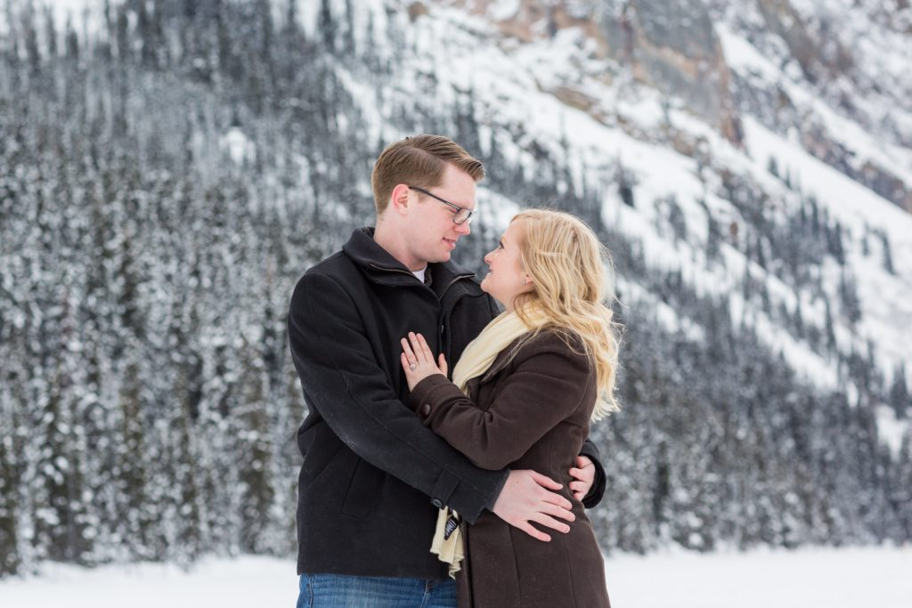 outdoor winter engagement photos with snowy trees behind