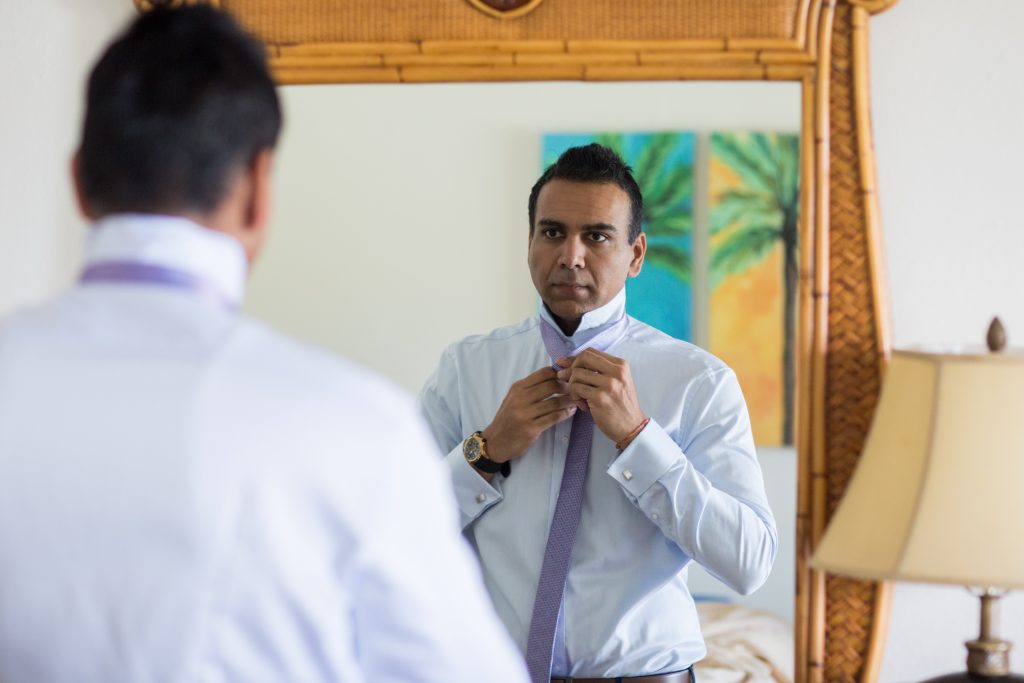 Groom getting ready tying his tie in the mirror
