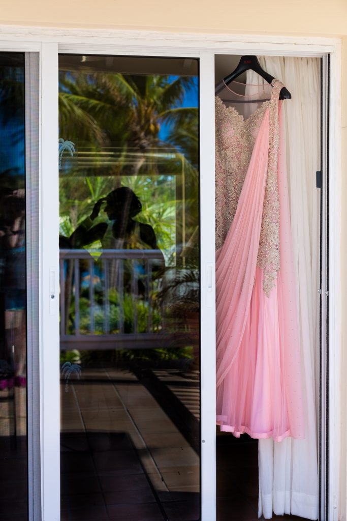 Pink bridal sari hanging up while the bride gets her makeup done before her Indian destination wedding ceremony