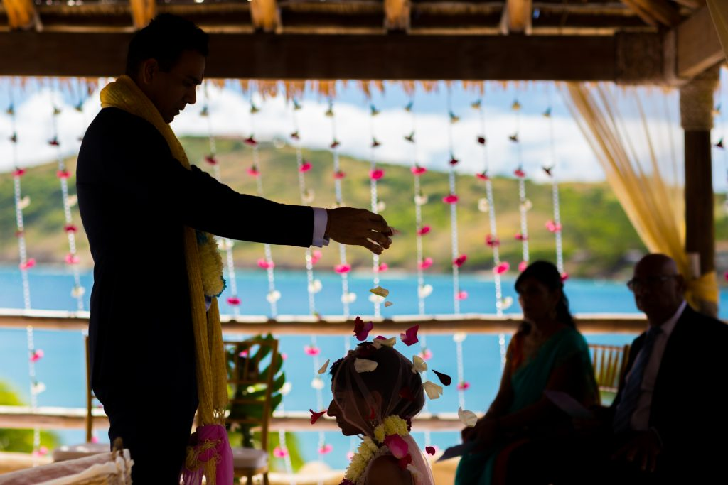 The groom showers his bride with rose petals during their romantic Antigua destination wedding