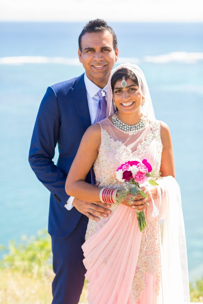 Bride and groom at the top of the cliffs overlooking the bay at St James Club in Antigua
