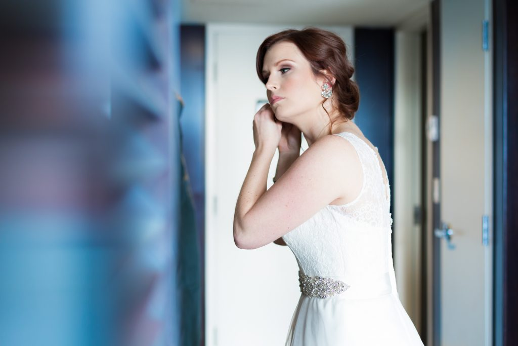 Photo of the bride putting on her earrings before Mosaic Centre Wedding portraits