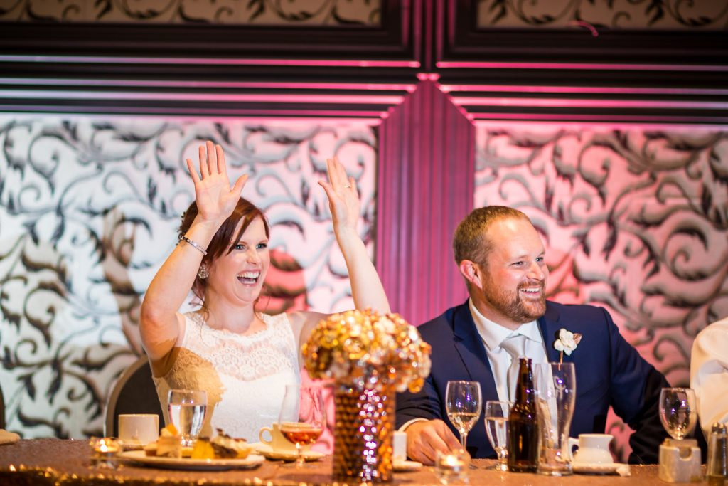 Bride and groom cheering for their wedding party as they give their speeches