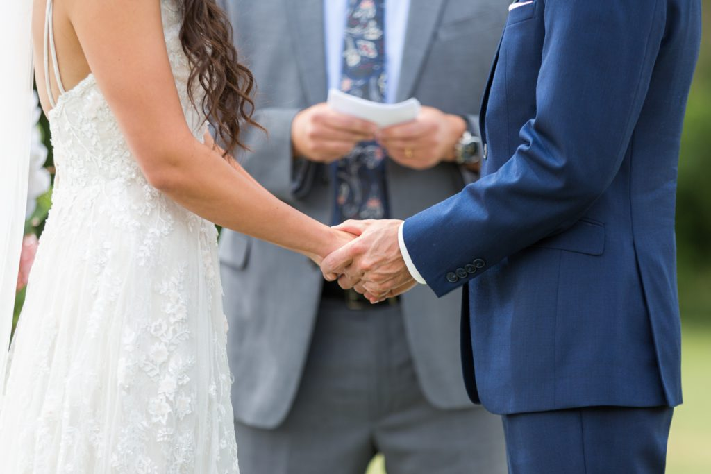 Bride and groom hold hands during the ceremony