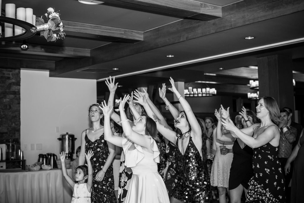 bridesmaids jumping to catch the bouquet