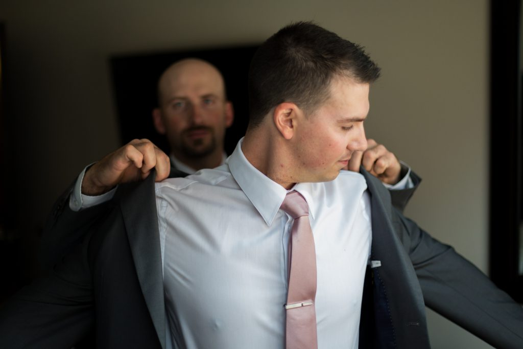 best man helping groom with his jacket