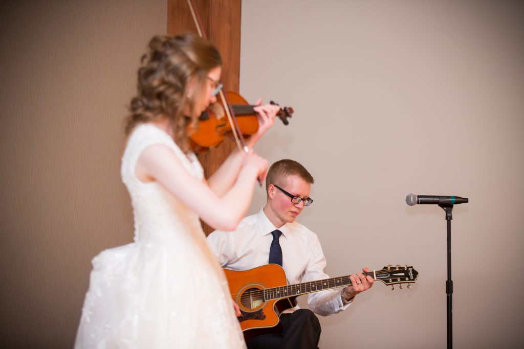 bride and groom playing music during wedding reception