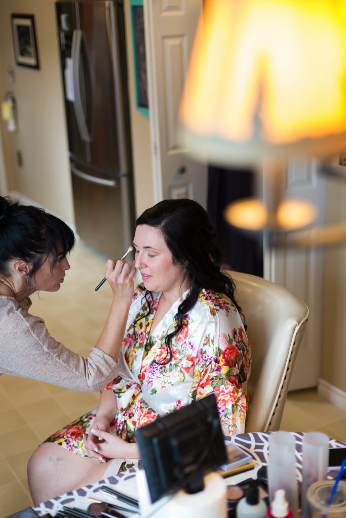 Bride in floral robe getting makeup done